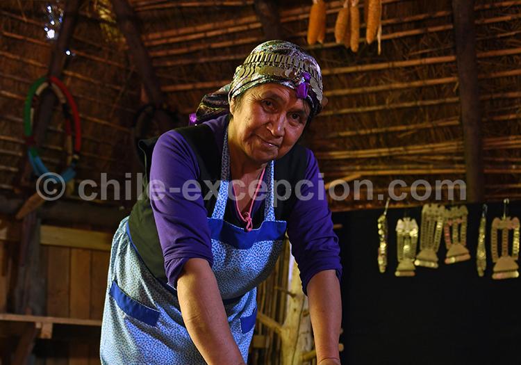 Dans une ruka, maison traditionnelle des indiens Mapuche, une femme moud le blé pour le pain traditionnel mapuche.