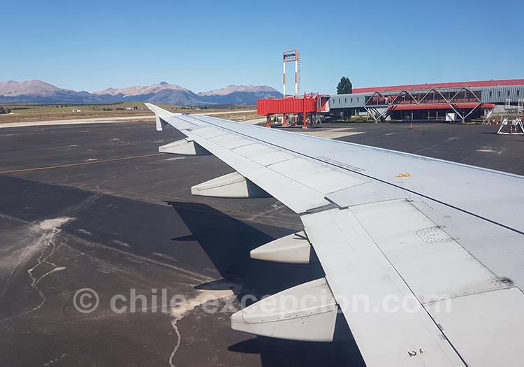 Atterrissage d'un avion à l'aéroport de Coyhaique, avec une vue sur l'aéroport et les Andes dans le fond